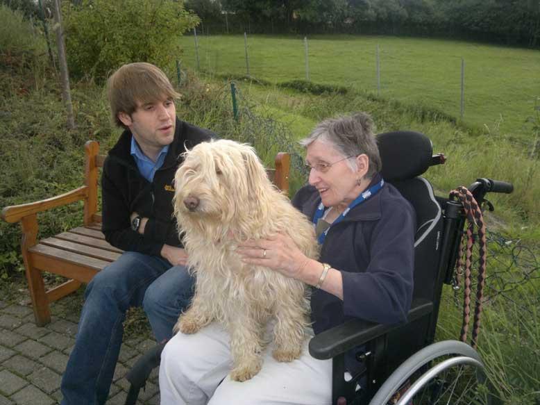 Bild Schifamhund auf Schoß einer Rollstuhlfahrerin